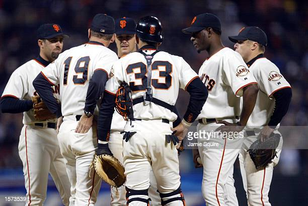 Pitching coach Dave Righetti of the San Francisco Giants discusses strategy on the mound with shortstop Rich Aurilia second baseman Jeff Kent catcher...
