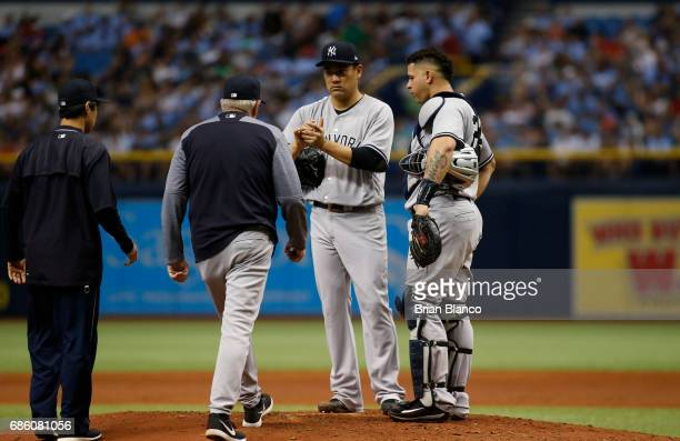Pitching coach Larry Rothschild of the New York Yankees and catcher Gary Sanchez come out to the mound to speak to pitcher Masahiro Tanaka after...