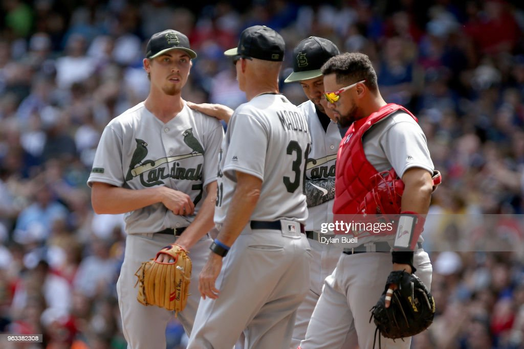 Pitching coach Mike Maddux meets with Luke Weaver #7 of the St. Louis Cardinals in the third inning against the Milwaukee Brewers at Miller Park on May 28, 2018 in Milwaukee, Wisconsin. MLB players across the league are wearing special uniforms to commemorate Memorial Day.