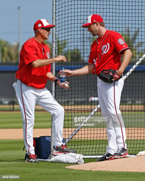 Pitching Coach Mike Maddux talks to Max Scherzer of the Washington Nationals during a morning workout prior to the spring training game against the...