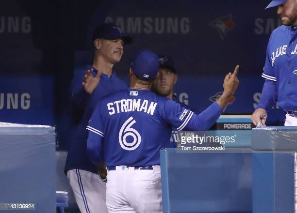 Pitching coach Pete Walker of the Toronto Blue Jays tries to soothe Marcus Stroman who reacts as he is taken out of the game in the seventh inning...