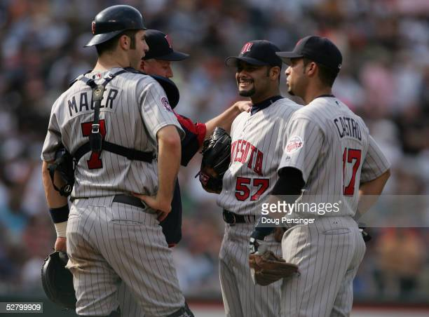 Pitching coach Rick Anderson makes a call to the mound to talk to starting pitcher Johan Santana along with teammates shortstop Juan Castro and...