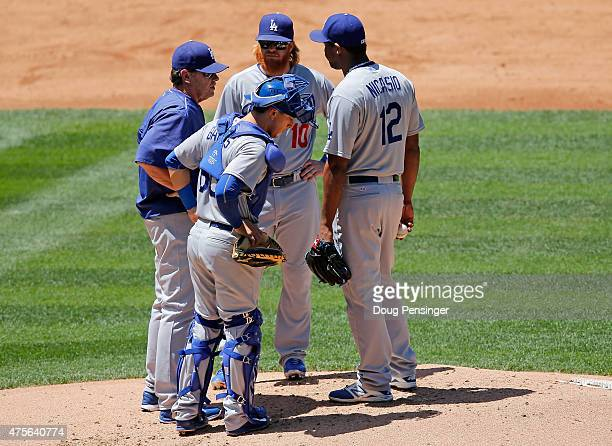 Pitching coach Rick Honeycutt of the Los Angeles Dodgers visits the mound to talk with starting pitcher Juan Nicasio of the Los Angeles Dodgers as...