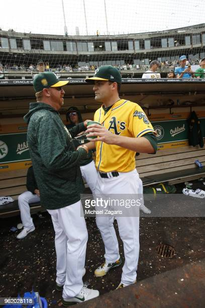 Pitching Coach Scott Emerson and Andrew Triggs of the Oakland Athletics talk in the dugout during the game against the Baltimore Orioles at the...