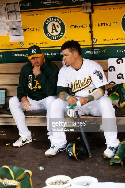 Pitching Coach Scott Emerson and Bruce Maxwell of the Oakland Athletics talk in the dugout during the game against the Kansas City Royals at the...