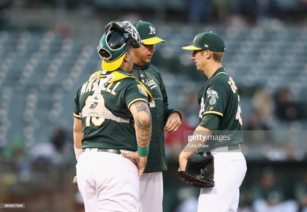 Pitching coach Scott Emerson #14 and catcher Bruce Maxwell #13 come out to talk to Daniel Gossett #48 of the Oakland Athletics after he gave up three home runs in a row to the Tampa Bay Rays in the third inning at Oakland Alameda Coliseum on May 29, 2018 in Oakland, California.