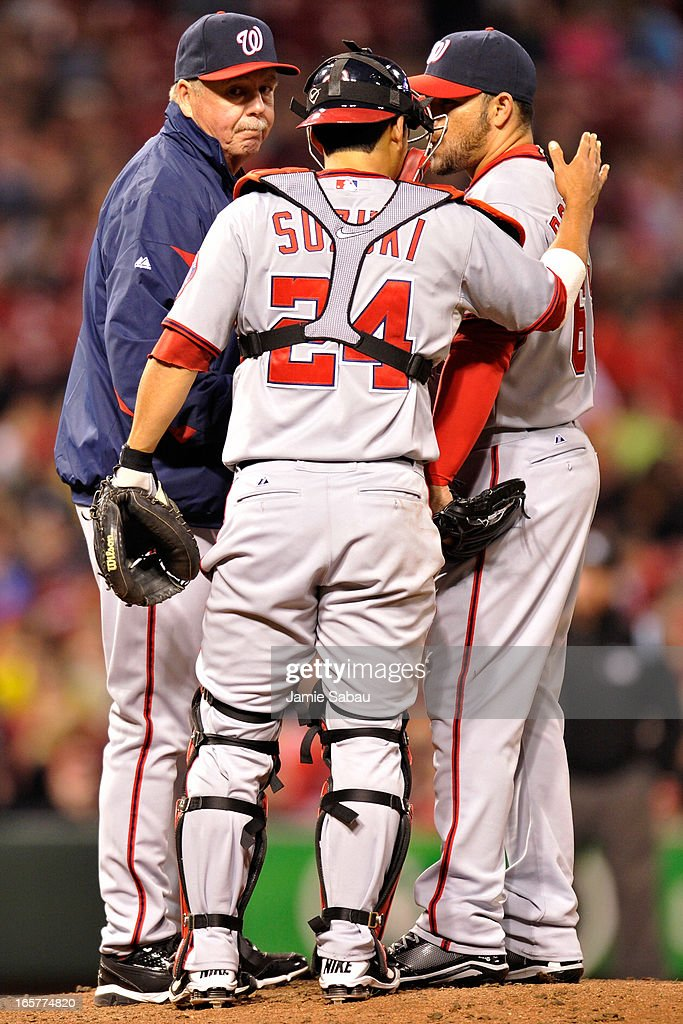 Pitching coach Steve McCatty of the Washington Nationals and catcher Kurt Suzuki #24 of the Washington Nationals visit with pitcher Henry Rodriguez #63 of the Washington Nationals on the mound in the seventh inning after Rodriguez gave up the sixth of six home runs hit by the Cincinnati Reds at Great American Ball Park on April 5, 2013 in Cincinnati, Ohio. Cincinnati defeated Washington 15-0.