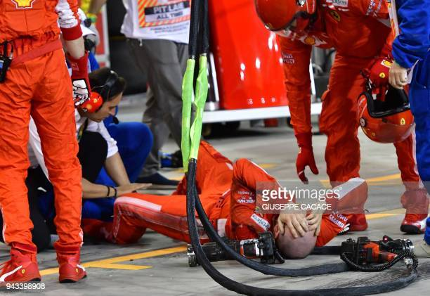 TOPSHOT A pitman lies on the ground after an accident during the pit stop of Ferrari's Finnish driver Kimi Raikkonen during the Bahrain Formula One...