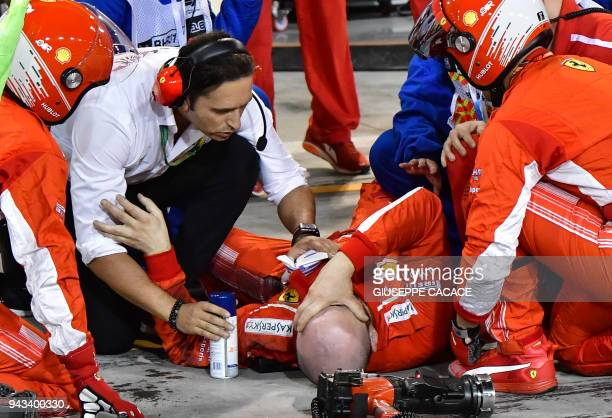A pitman receives medical assistant following an accident during the pit stop of Ferrari's Finnish driver Kimi Raikkonen during the Bahrain Formula...