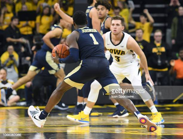 Pitt Panthers guard Xavier Johnson tries to pass the ball around Iowa Hawkeyes guard Jordan Bohannon during a nonconference college basketball game...