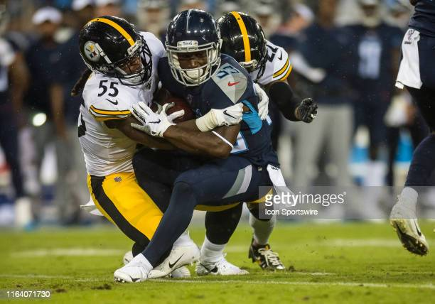 Pittsburg Steelers linebacker Devin Bush and cornerback Steven Nelson tackle Tennessee Titans running back Dion Lewis during a game between the...