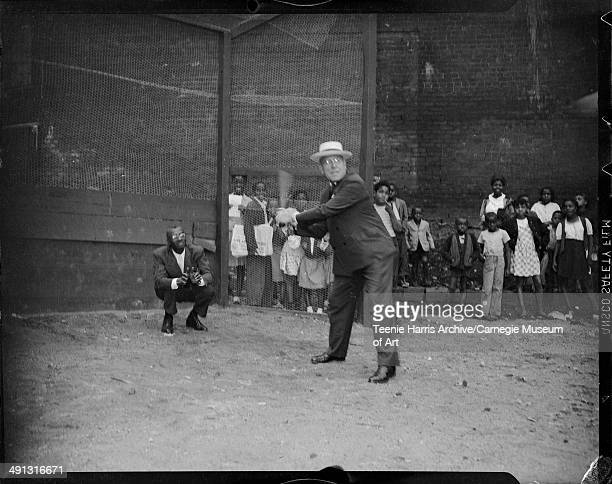 Pittsburgh Mayor David L Lawrence swinging baseball bat in dirt lot with wood and screening batting cage with man wearing suit acting as catcher and...
