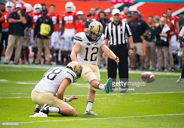 Pittsburgh Panthers Kicker Chris Blewitt kicks the ball as Pittsburgh Panthers Punter Ryan Winslow holds the ball during the NCAA football game...