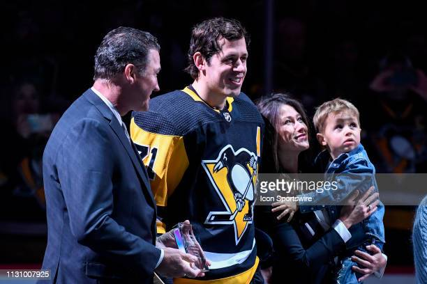 Pittsburgh Penguins Center Evgeni Malkin and his wife Anna Kasterova and son Nikita smile during a pregame ceremony honor Malkin's 1000 NHL career...