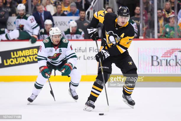 Pittsburgh Penguins Center Evgeni Malkin moves the puck in front of Minnesota Wild Left Wing Zach Parise during the first period in the NHL game...