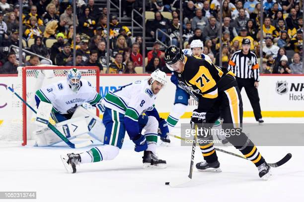 Pittsburgh Penguins Center Evgeni Malkin shoots the puck while Vancouver Canucks Defenseman Chris Tanev defends in front of Vancouver Canucks Goalie...