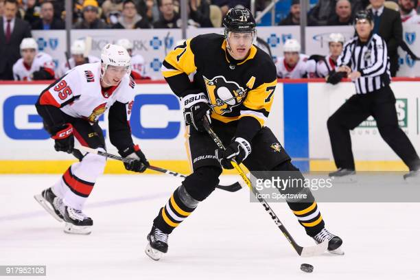 Pittsburgh Penguins Center Evgeni Malkin skates with the puck ahead of Ottawa Senators Center Matt Duchene during the first period in the NHL game...