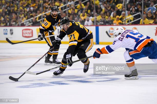 Pittsburgh Penguins center Evgeni Malkin skates with the puck around New York Islanders right wing Cal Clutterbuck during the second period in Game 3...
