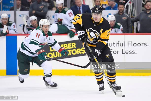 Pittsburgh Penguins Center Evgeni Malkin skates with the puck in front of Minnesota Wild Left Wing Zach Parise during the first period in the NHL...