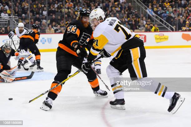 Pittsburgh Penguins Center Evgeni Malkin spins and shoots the puck while Philadelphia Flyers Right Wing Jakub Voracek defends in front of...