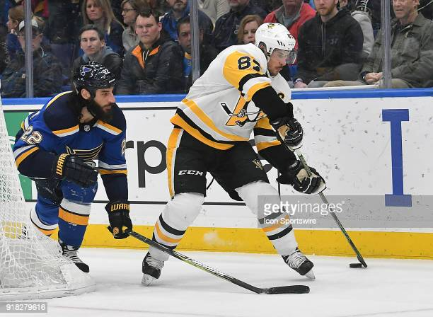 Pittsburgh Penguins center Sidney Crosby controls the puck behind the net with pressure from St Louis Blues right wing Chris Thorburn during a NHL...