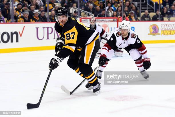 Pittsburgh Penguins Center Sidney Crosby handles the puck in front of Arizona Coyotes Defenseman Niklas Hjalmarsson during the second period in the...