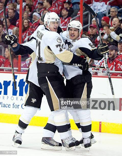 Pittsburgh Penguins center Sidney Crosby right celebrates with teammates Pittsburgh Penguins center Evgeni Malkin and right wing Pascal Dupuis rear...