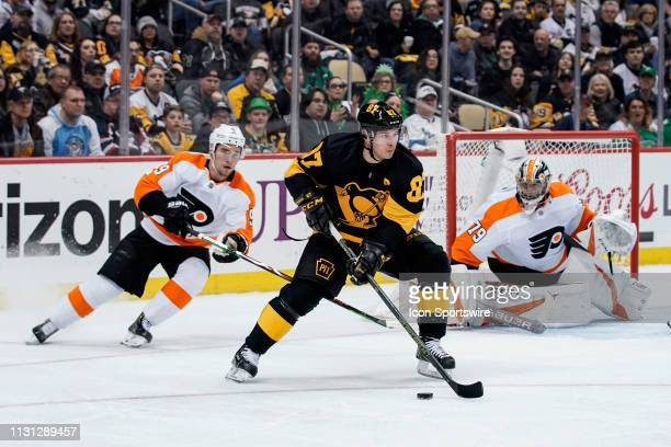 Pittsburgh Penguins Center Sidney Crosby skates with the puck around the net while Philadelphia Flyers Defenseman Ivan Provorov defends and...