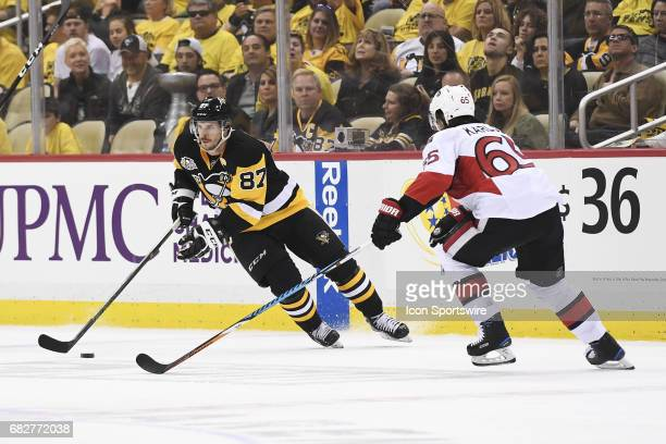 Pittsburgh Penguins Center Sidney Crosby skates with the puck infant of Ottawa Senators defenseman Erik Karlsson during the second period in Game One...