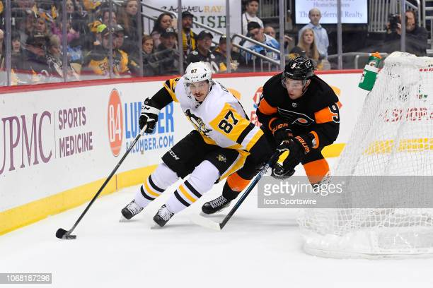 Pittsburgh Penguins Center Sidney Crosby skates with the puck while holding off Philadelphia Flyers Defenseman Ivan Provorov during the first period...