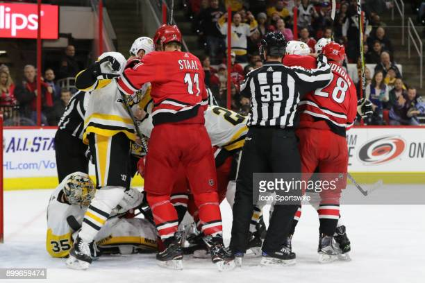 Pittsburgh Penguins Defenceman Brian Dumoulin pushes Carolina Hurricanes Center Jordan Staal while line judge Rusty Baynes tries to break up the...
