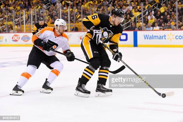 Pittsburgh Penguins defenseman Jamie Oleksiak skates with the puck while Philadelphia Flyers left wing Michael Raffl forechecks during the third...