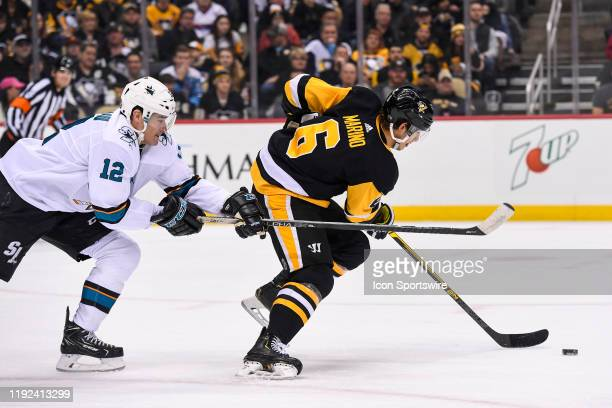 Pittsburgh Penguins Defenseman John Marino skates with the puck under pressure from San Jose Sharks Winger Patrick Marleau during the first period in...