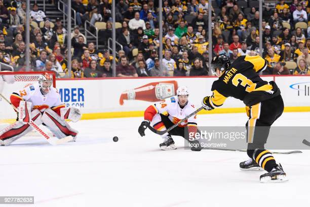 Pittsburgh Penguins Defenseman Olli Maatta shoots the puck on Calgary Flames Goalie Jon Gillies while Calgary Flames Defenseman Travis Hamonic...