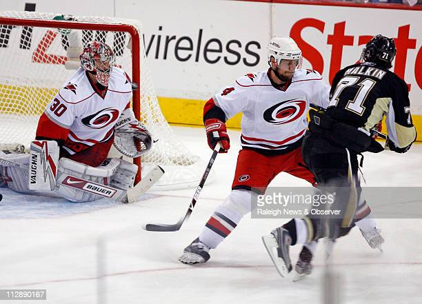 Pittsburgh Penguins' Evgeni Malkin puts the puck past Carolina Hurricanes' Cam Ward's shoulder and defender Dennis Seidenberg as he scored his third...