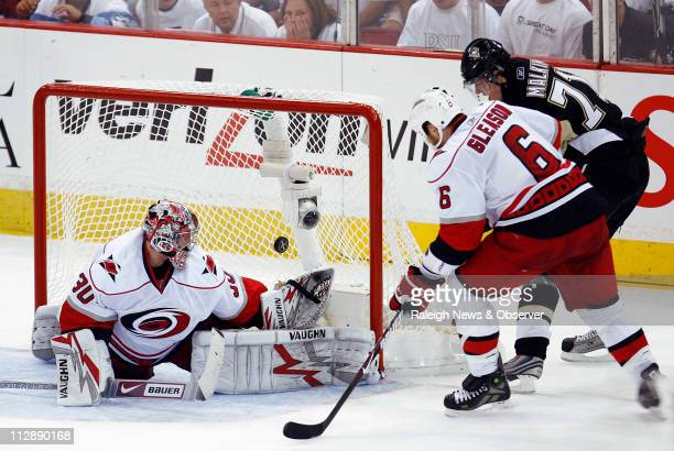 Pittsburgh Penguins' Evgeni Malkin puts the puck past Carolina Hurricanes' Cam Ward and defender Tim Gleason for his second of three goals on the...