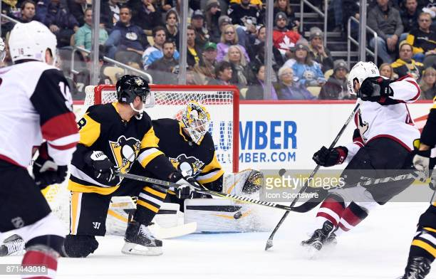 Pittsburgh Penguins Goalie Matt Murray makes a save on Arizona Coyotes Defenseman Jason Demers in front during the first period in the NHL game...