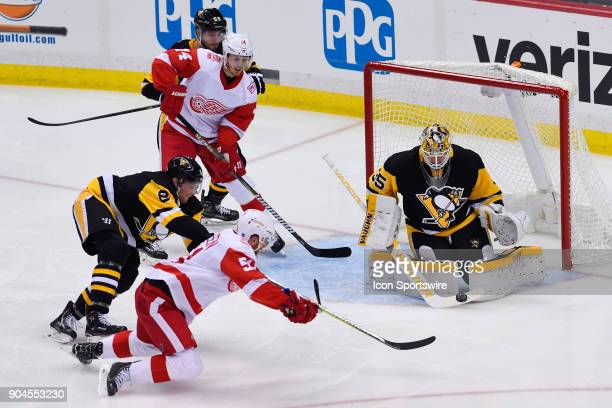 Pittsburgh Penguins Goalie Tristan Jarry makes a save on Detroit Red Wings Center Frans Nielsen in front as Pittsburgh Penguins Defenseman Brian...