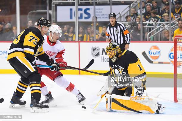 Pittsburgh Penguins goaltender Casey DeSmith makes a save with Detroit Red Wings Evgeny Svechnikov and Pittsburgh Penguins defenseman Jack Johnson...