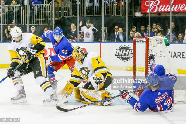 Pittsburgh Penguins goaltender Casey DeSmith tries to cover loose puck as New York Rangers defenseman John Gilmour and Pittsburgh Penguins defenseman...