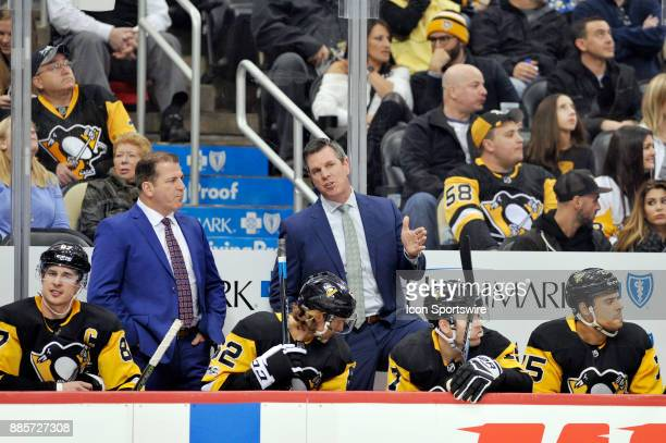 Pittsburgh Penguins head coach Mike Sullivan and assistant coach Mark Recchi talk on the bench during the second period in the NHL game between the...
