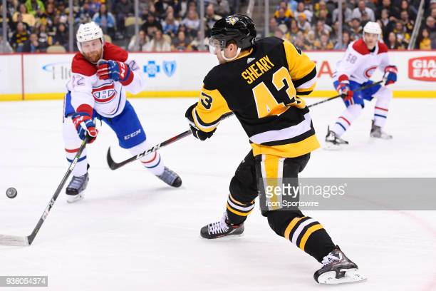 Pittsburgh Penguins Left Wing Conor Sheary shoots the puck while Montreal Canadiens Defenseman Karl Alzner defends during the second period in the...