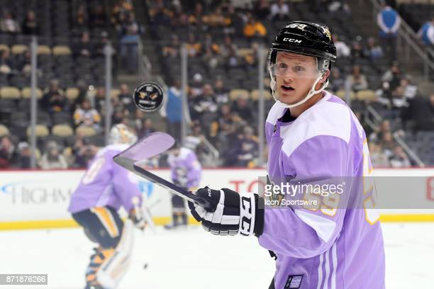 Pittsburgh Penguins Left Wing Jake Guentzel bounces the puck off his stick in warms up wearing a special 'Hockey Fights Cancer' jersey before the NHL...
