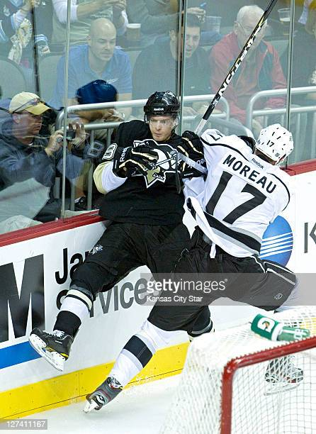 Pittsburgh Penguins right wing Nick Johnson ends up against the glass on a check by Los Angeles Kings left wing Ethan Moreau during Tuesday's...
