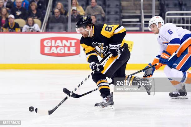 Pittsburgh Penguins Right Wing Phil Kessel skates with the puck ahead of New York Islanders Defenseman Ryan Pulock during the second period in the...