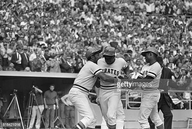 Pittsburgh Pirates Al Oliver is grabbed by teammates Willie Stargell and Roberto Clemente after his threerunhomer which gave the Pirates a 95 victory...