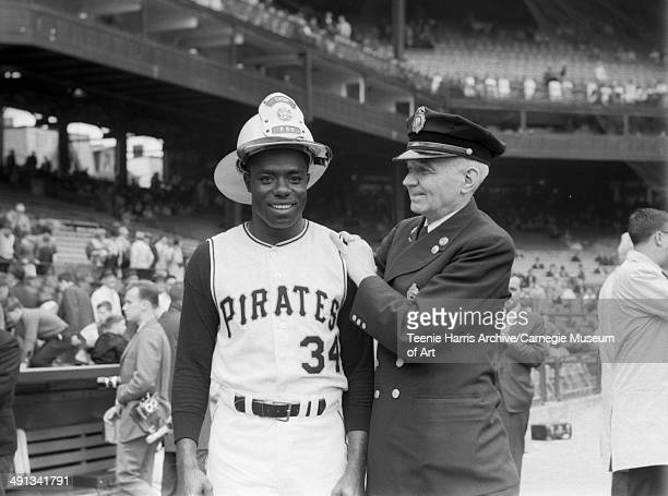 Pittsburgh Pirates baseball player Al McBean wearing fireman's hat, and unknown fire fighter wearing dress uniform, standing on Forbes Field for 1965...
