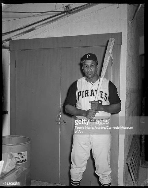 Pittsburgh Pirates baseball player Willie Stargell posing with bat in front of closet door next to barrel of Witt's Green Sweeping Compound...