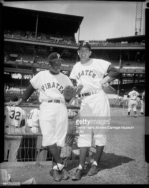 Pittsburgh Pirates baseball players Curtis 'Curt' Roberts holding glove and Frank Thomas leaning against dugout fence at Forbes Field Pittsburgh...