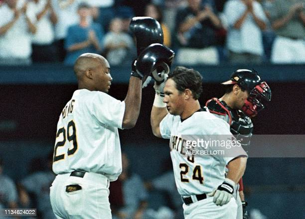 Pittsburgh Pirates' Brian Giles taps helmets with teammate Kevin Young beside Atlanta Braves' catcher Eddie Perez after Giles hit his first of two...